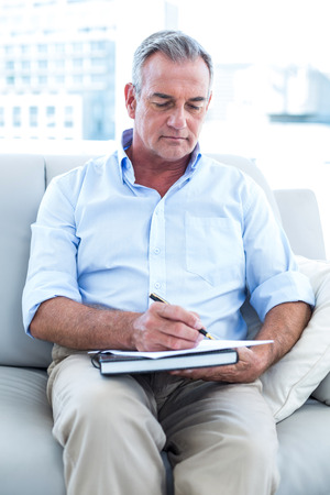 person writing: High angle view of businessman writing on notepad at office