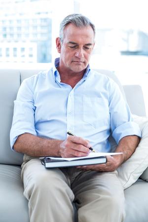 persona escribiendo: Vista de ángulo alto del hombre de negocios por escrito en la libreta en la oficina