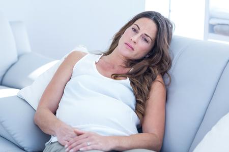 gente triste: Vista de �ngulo alto de la mujer embarazada triste apoy�ndose en el sof� en casa