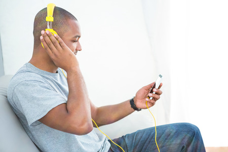 listening device: Young man listening music on smartphone at home Stock Photo