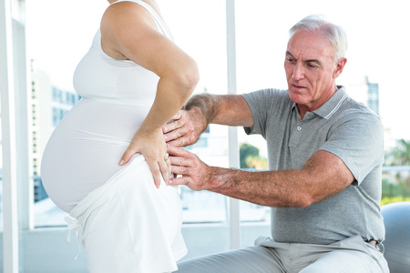 health club: Therapist massaging back of pregnant woman at health club Stock Photo