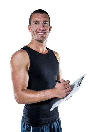 sports coach: Portrait of smiling sports coach writing on clipboard against white background