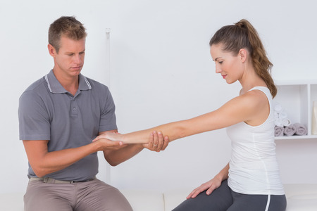strength therapy: Doctor stretching a young woman arm in medical office Stock Photo