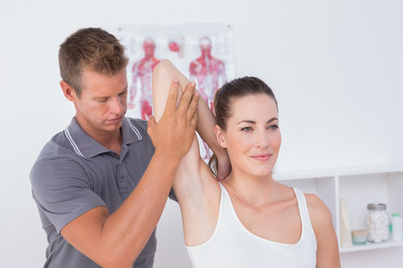 mobilization: Doctor examining his patient arm in medical office Stock Photo