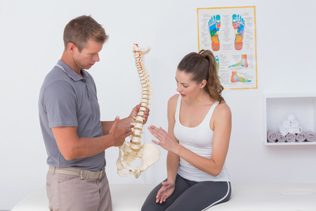 pain: Doctor showing anatomical spine to his patient in medical office Stock Photo