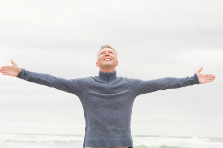 short wave: Man standing with arms out wide at the beach