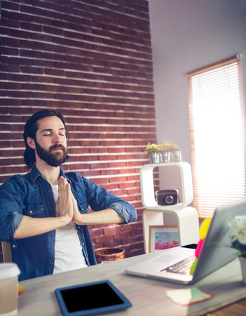 clasped hand: Businessman with hand clasped meditating in creative office Stock Photo