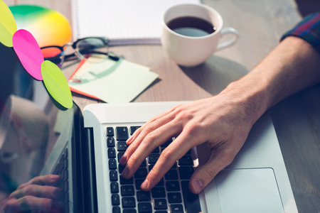 Cropped hand of graphic designer working on laptop in office