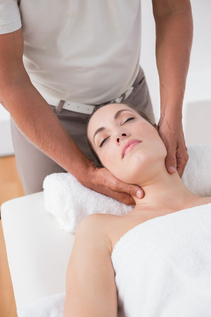 neck massage: Woman receiving neck massage in medical office Stock Photo