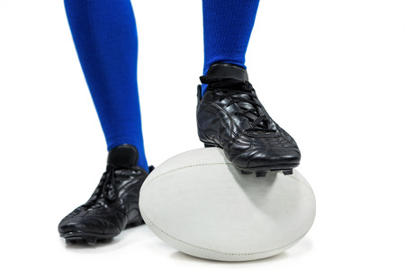 blue ball: Low section of of rugby player on ball against white background Stock Photo