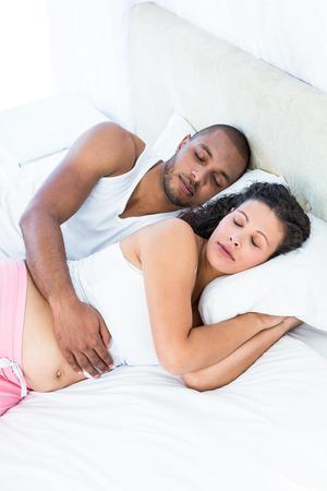 mujer en la cama: Vista de ángulo alto de la mujer embarazada con el marido duerme en el país