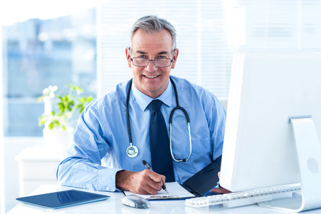 doctor of medicine: Portrait of smiling male doctor writing data at desk in hospital Stock Photo