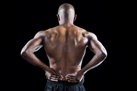 hand on hip: Rear view of athlete stretching with hand on hip against black background