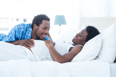 pregnant woman with husband: Smiling husband looking at his wife while relaxing on bed Stock Photo
