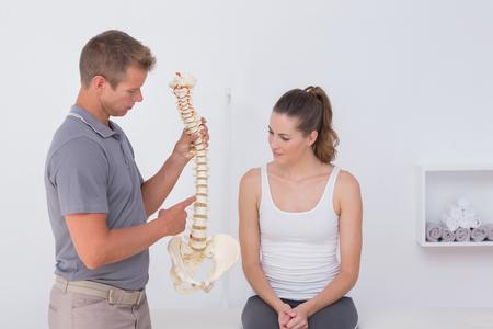 mujeres de espalda: Doctor que muestra la columna vertebral anat�mica a su paciente en el consultorio m�dico Foto de archivo