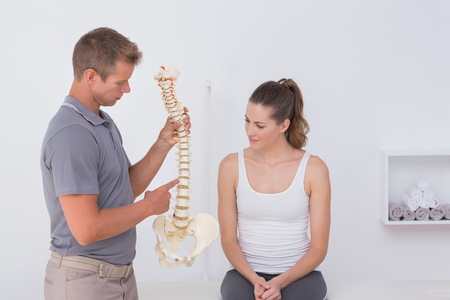 Doctor showing anatomical spine to his patient in medical office Stock Photo
