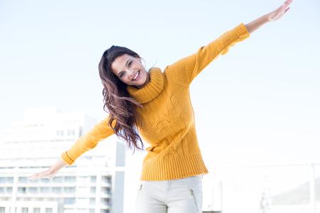 глядя на камеру: Счастливая женщина, глядя камеры с поднятыми руками на улице