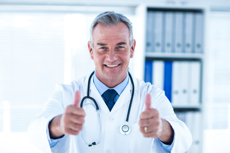 thumps up: Portrait of smiling male doctor showing thumps up sign in clinic Stock Photo