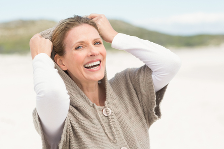 sunlit: Smiling woman standing on the sand with hood up at the beach Stock Photo