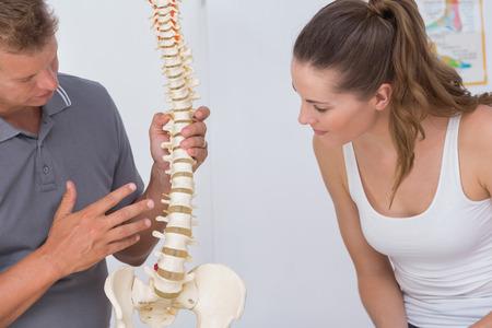 personas de espalda: Doctor que muestra la columna vertebral anatómica a su paciente en el consultorio médico Foto de archivo