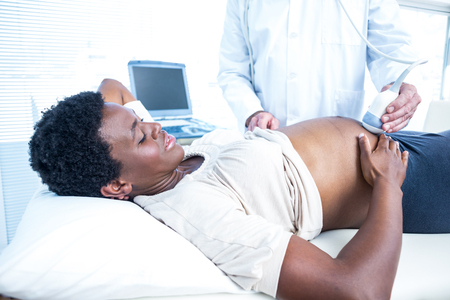 mid adult women: Doctor using ultrasound machine on pregnant woman in clinic