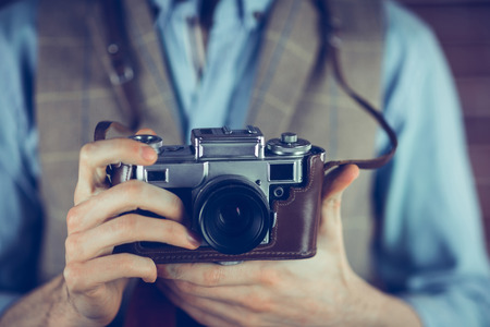 digital camera: Midsection of man holding camera Stock Photo