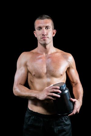 hombres negros: Retrato de hombre sin camisa guapo sosteniendo suplemento nutricional contra el fondo negro