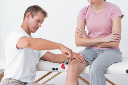 physiotherapy: Doctor examining his patient knee in medical office Stock Photo