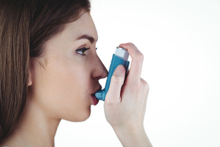 asthmatic: Asthmatic brunette using her inhaler on white background