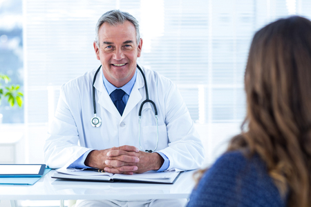 mature male: Portrait of male doctor sitting with woman at desk in hospital
