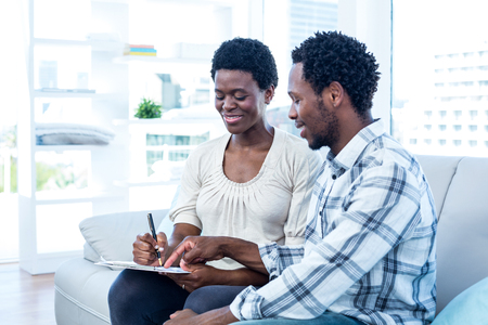 wife and husband: Happy man talking with pregnant wife while pointing on paper at home Stock Photo