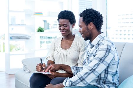 marido y mujer: Hombre feliz que habla con la mujer embarazada mientras apuntando en papel como en casa