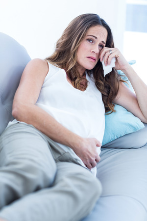 adult crying: Portrait of sad pregnant woman relaxing on sofa at home