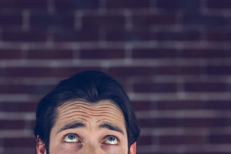 eyebrow raised: Confused man with raised eyebrows against brick wall