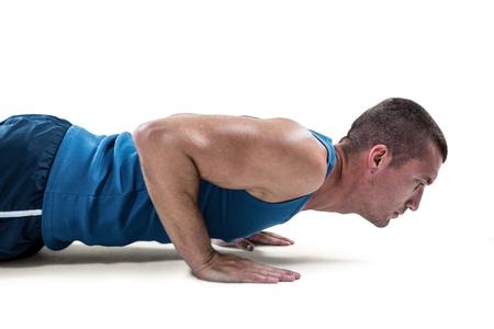 push ups: Man in sportswear doing push ups against white background