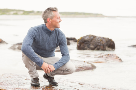 crouched: Man crouched down on a large rock by the shore