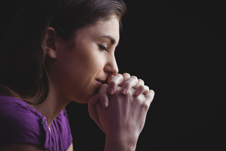Woman praying with hands together on black background Stock Photo