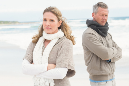 exasperated: Upset couple look away from each other at the beach Stock Photo