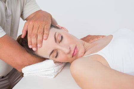 massaggio collo: Woman receiving neck massage in medical office Archivio Fotografico