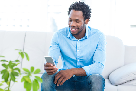 classy house: Smiling man using smartphone while sitting on sofa at home