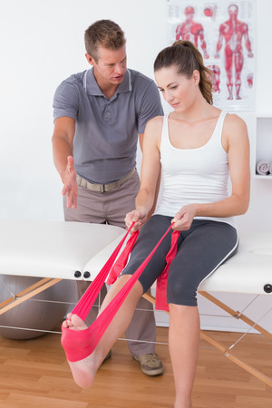 muscle retraining: Doctor examining his patient back legs in medical office Stock Photo