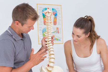 herniated: Doctor showing anatomical spine to his patient in medical office Stock Photo
