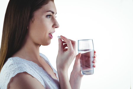 Pretty woman taking white pill on white background