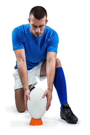 by placing: Full length of rugby player placing ball against white background Stock Photo