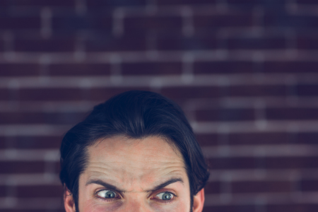angry person: Hombre enojado con las cejas levantadas mirando a otro lado contra la pared de ladrillo