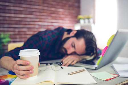 sleeping at desk: Tired creative editor holding disposable cup while sleeping on office desk