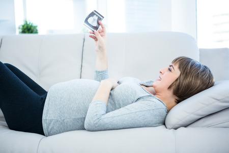 sonogram: Hermosa mujer embarazada mirando sonograma mientras est� acostado en el sof� en casa Foto de archivo