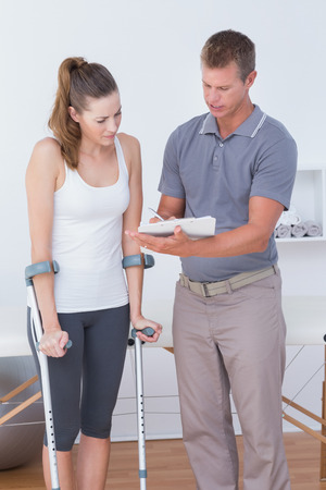 retraining: Woman with crutch speaking with his doctor in medical office