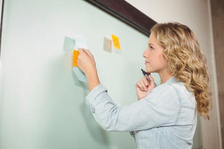 board marker: Thoughtful woman holding marker by glass board in office