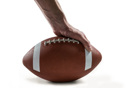 american football: Close-up of American football player holding ball against white background Stock Photo